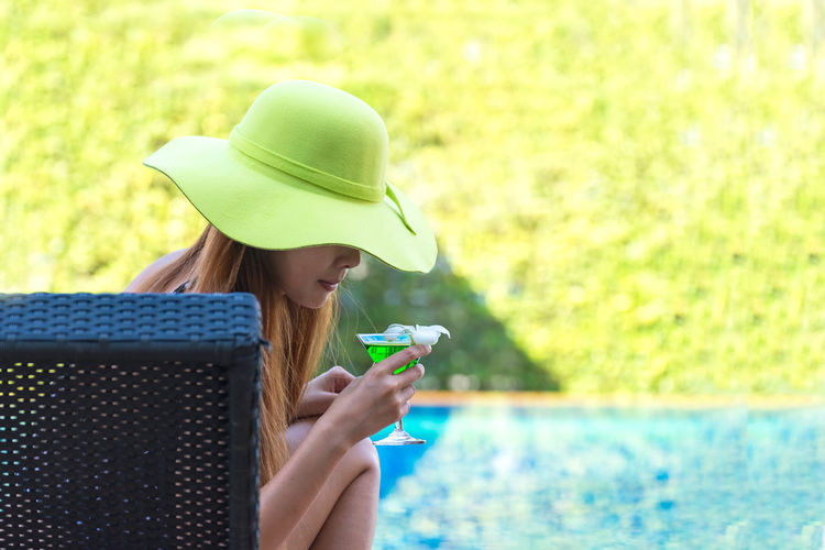 Portrait of woman holding hat in swimming pool