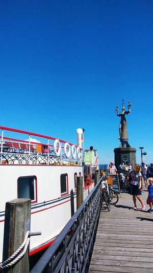Statue of people on bridge against blue sky