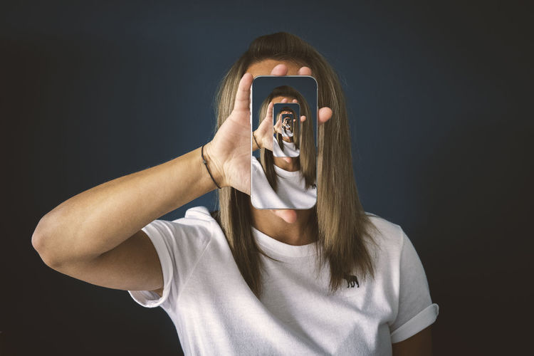 Portrait of teenage girl photographing against black background