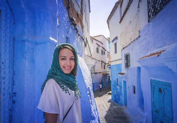 """""""The Blue City"""" We travelled from Sevilla to Tarifa, then took a ferry to Tangier, then a taxi to Chefchaouen, Morocco. EyeEmNewHere a new beginning Chefchaouen Morocco Beauty Blue City Blue Medina Looking At Camera Portrait One Person Young Women Young Adult Women Headscarf Beautiful Woman Scarf Front View Lifestyles Outdoors Day Smiling Leisure Activity Happiness Built Structure Digital Nomad Standing Building Exterior Warm Clothing Real People Clothing"""