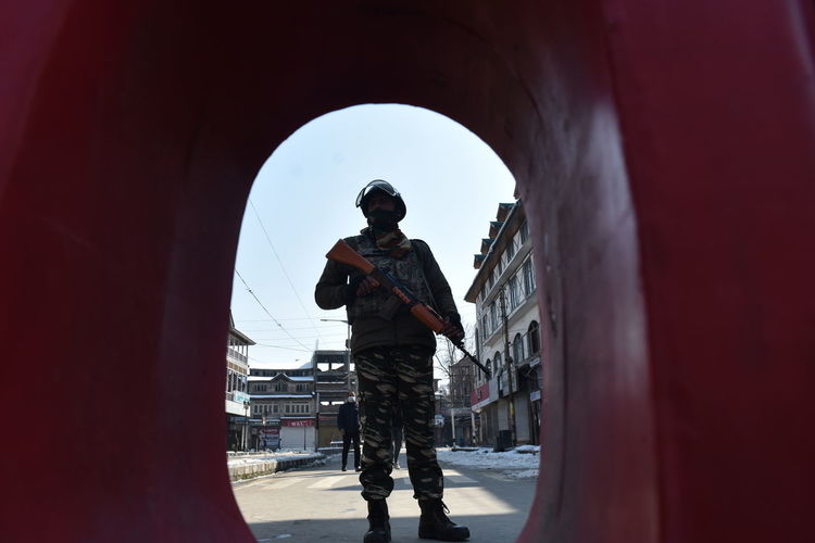 A paramilitary slider stands guard during shutdown In SRINAGAR .Strike was observed in Srinagar and other parts of Kashmir valley in connection with the sixth death anniversary of Mohammad Afzal Guru on Saturday Kashmir , India Srinagar Kashmir Policeman Solider Guard  Standing Men