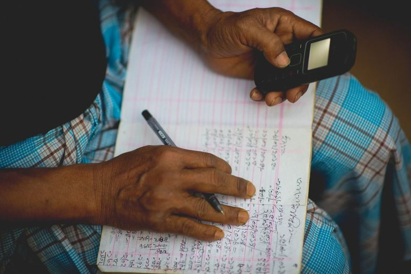 Midsection of man doing calculation with book and mobile phone at home