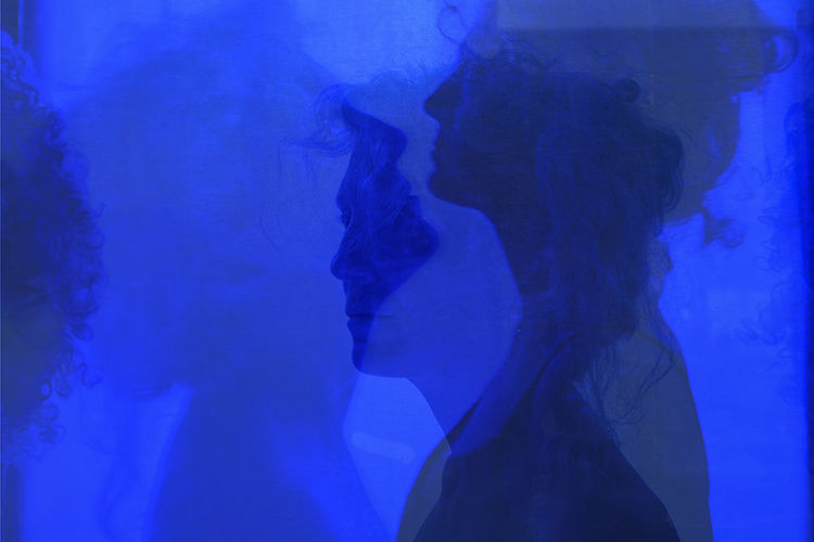 Close-up of woman standing against blue background