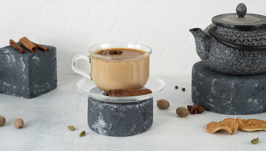 Masala tea or chai in a glass cup with traditional teapot on pedestal. indian drink with spicy, milk