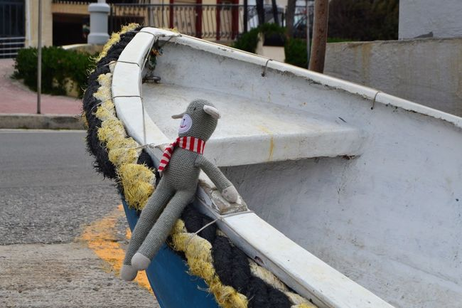 Little Man (a knitted dog toy) wearing a red and white striped scarf sitting on a fishing boat in Malta. We forgot to send him on his holidays to the kennels with our dog, so we took him with us to Malta for a trip of a lifetime! Adult Adults Only Architecture Boat Building Exterior City Day Dog Toy Fishing Boat Flexibility Fun Photography Grey Knitted Toy Little Man   One Man Only One Person Only Men Outdoors People Scarf Steps Steps And Staircases