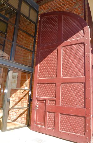 Unique tall red door accent on building exterior with glass entryway in Fremantle, Western Australia. Accent Architecture Brick Building Building Exterior Built Structure Closed Day Design Door Doorway Entrance Exterior Fremantle  Outdoors Red Shadow Sunny Tall - High Textured  Unique Wall Western Australia Windows Wooden