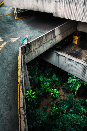 High Angle View Of Man Sitting On Bridge