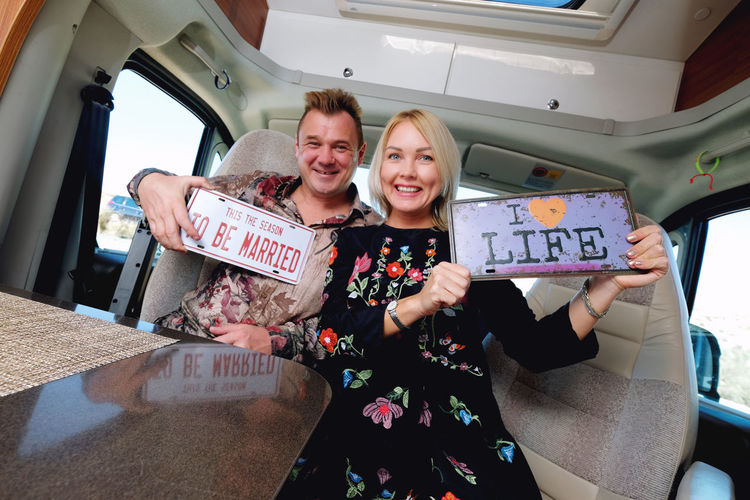 Portrait of smiling couple with message sitting in motor home