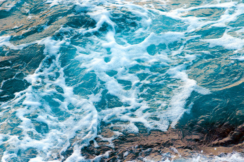 Foamy water waves at the ocean, view from above. top view sea texture. photo with motion blur.