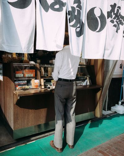 Salaryman buying a bento box for lunch break. Real People Standing Men Lifestyles Day People Rush Hour Tokyo Street Photography Tokyo Salaryman Business Businessman Sugamo Streetphotography