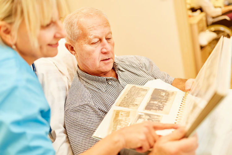 Nurse pointing at photo album with man at home