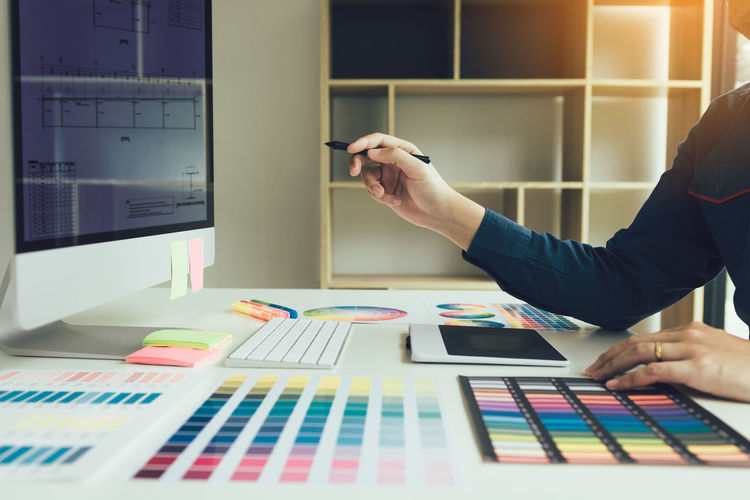 Cropped hand of businesswoman analyzing color swatch at desk in office