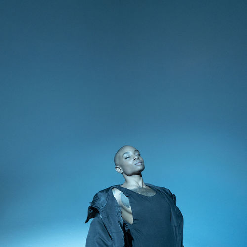 Bald young woman with eyes closed standing against blue background