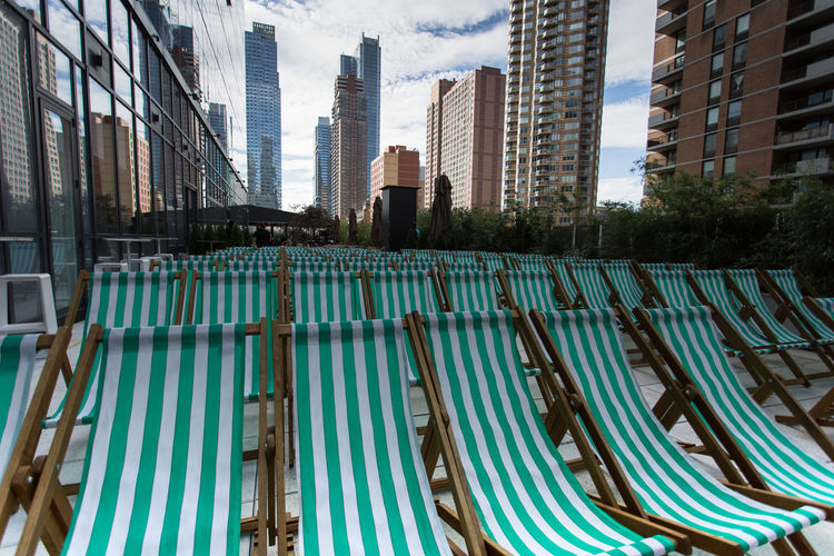 Green deck chairs amidst modern buildings in city
