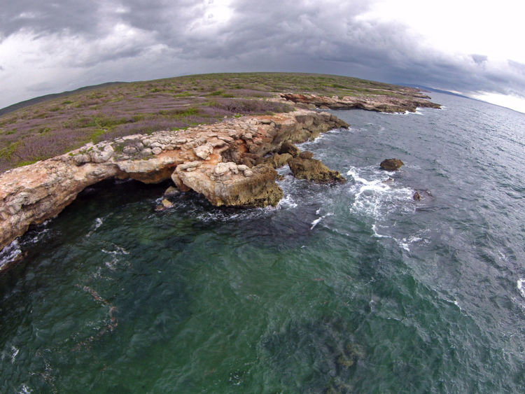 A rocky coastline on the Eastern coast of Puerto Rico with a cave system. It is a fisheye lens and the curvature of the horizon and coloration of the land and water simulate the globe from space. A Bird's Eye View Cliff Cloud - Sky Coastline Day High Angle View Nature Non-urban Scene Ocean Outdoors Rock - Object Rocky Coastline Scenics Sea Sky Tourism Tranquil Scene Water Waterfront