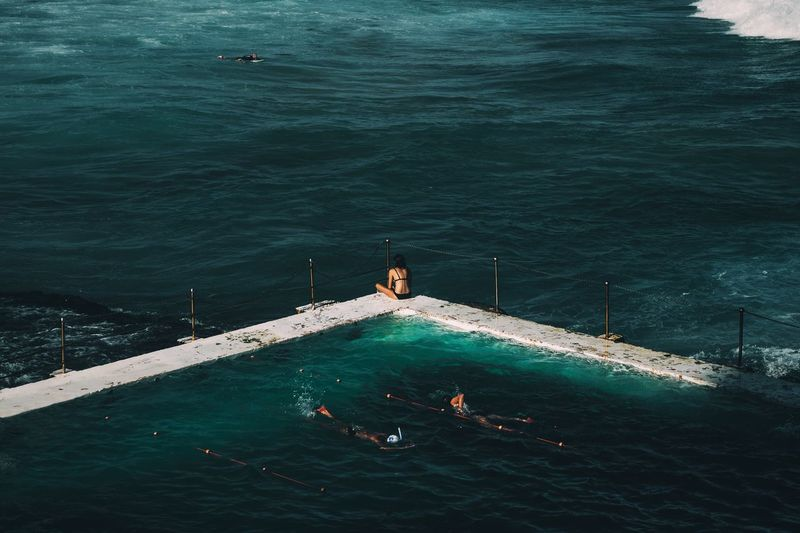 People in swimming pool against calm blue sea