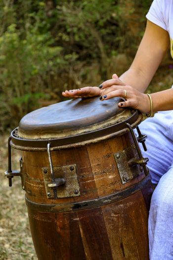 Midsection of woman playing drum outdoors