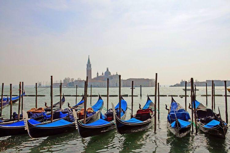 Gondolas moored at pier with church of san giorgio maggiore in background