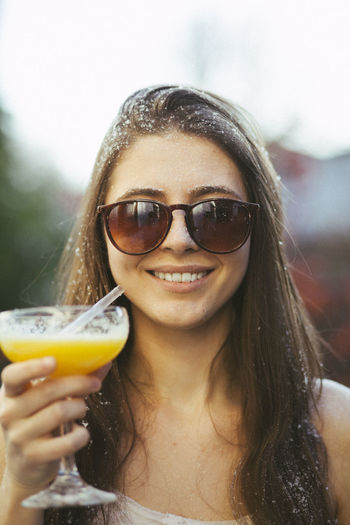 Portrait Of Young Woman With Cocktail Wearing Sunglasses