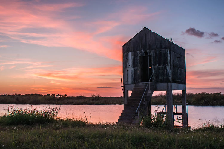 Sunset behind an old farming pump house on a Lake Okeechobee rim canal, Belle Glade, Florida. Belle Glade Pump House Architecture Beauty In Nature Building Exterior Built Structure Cloud - Sky Day Farming Relic Grass Lake Lake Okeechobee Nature No People Old Equipment Outdoors Reclaimed By Nature Scenics Sky Sunset Tranquil Scene Tranquility Water