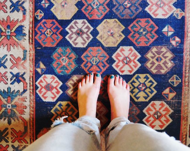 Low section of woman standing on carpet
