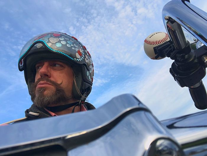 Low Angle View Of Man Sitting On Motorcycle Against Sky