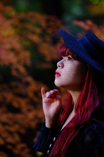 Side View Of Thoughtful Redhead Woman With Hat Against Trees
