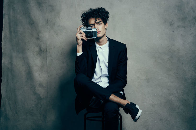 Young man photographing against wall
