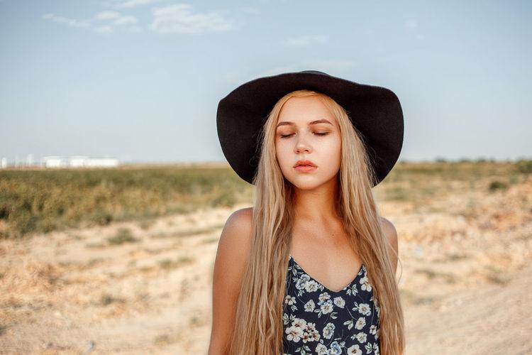 Teenage girl wearing hat against sky
