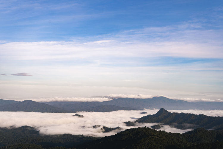 Scenic view of cloudscape over mountains against sky
