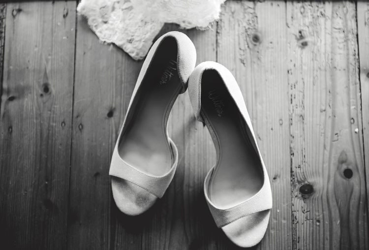 Close-up of shoes on wooden plank