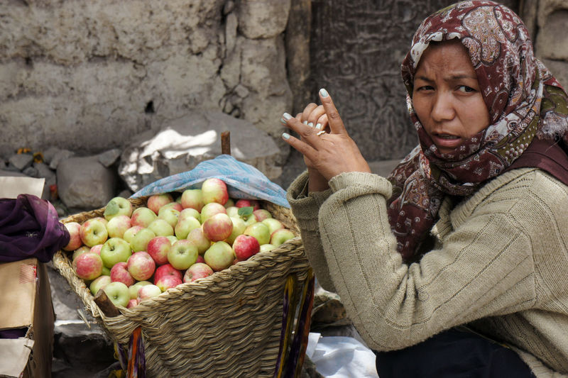 Full length of woman holding fruits at market stall