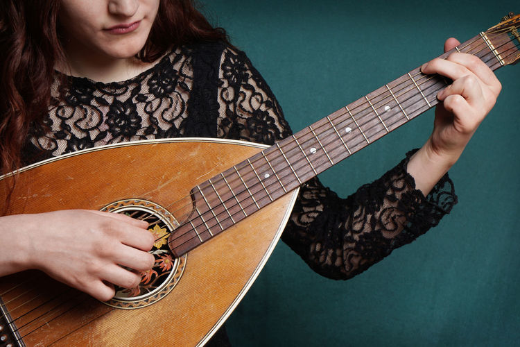 Midsection of woman playing lute against wall