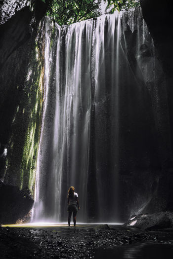 Full length of young woman standing by waterfall
