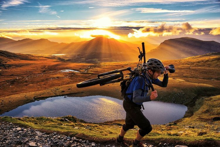 Side view of man carrying bicycle on shoulder in front of mountains during sunset