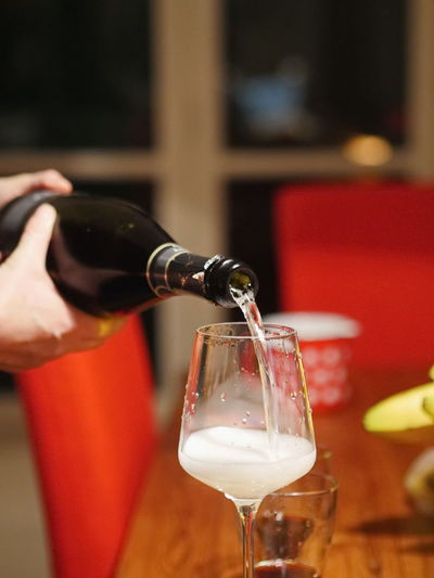 Cropped image of hands pouring wine in glass on table