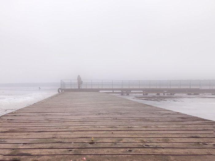 Pier Over Sea Against Foggy Sky