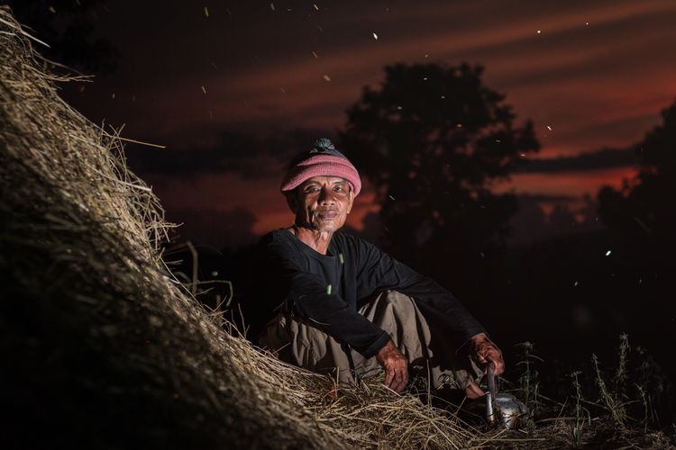 Portrait of farmer sitting on hay at field during night