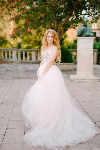 Portrait of bride wearing white dress standing outdoors