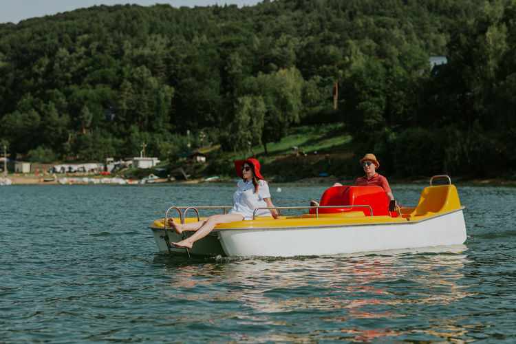 Couple in love enjoying boating in the lake. Portrait of young man and woman pedal boating on the river. Boating Couple Date Holiday Horizontal Love Man Romantic Summertime Vacations Woman Young Boat Boyfriend Caucasian Day Girlfriend Lake Outdoors Pedalo Relax Sea Summer Two People Water