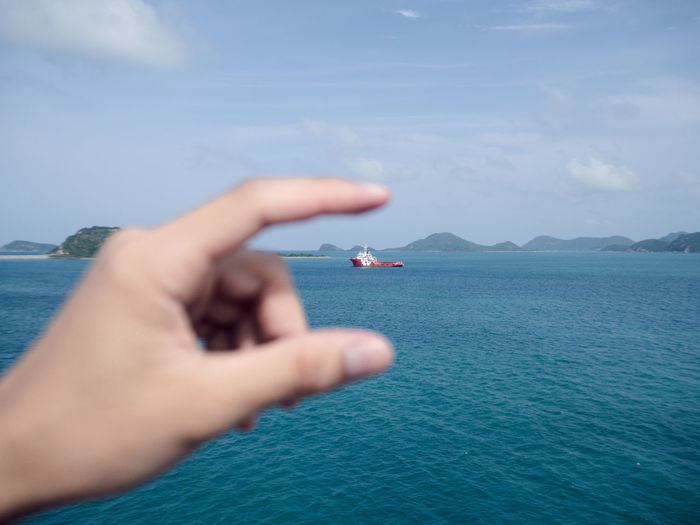 Cropped hand gesturing against boat in sea