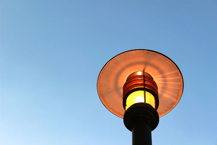 Low angle view of illuminated gas light against clear blue sky