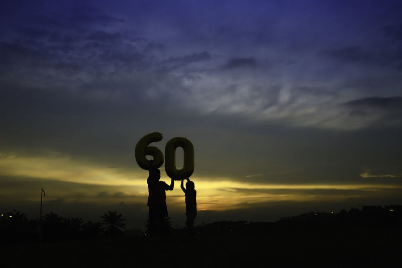 Silhouette boys holding number 60 balloon against sky during sunset