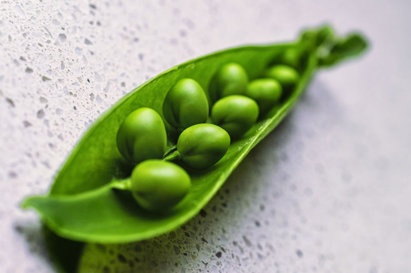 Close-up of green peas in pod on floor