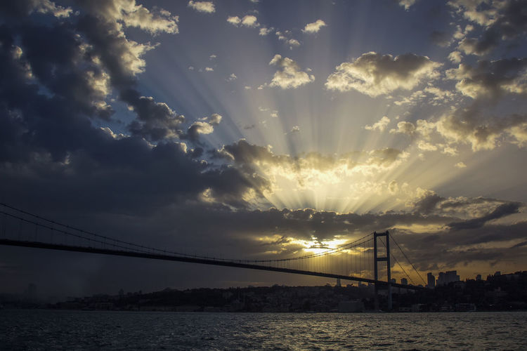 Bridge over bay against sky during sunset