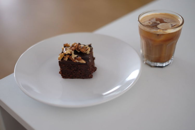 High angle view of brownie in plate with coffee on table