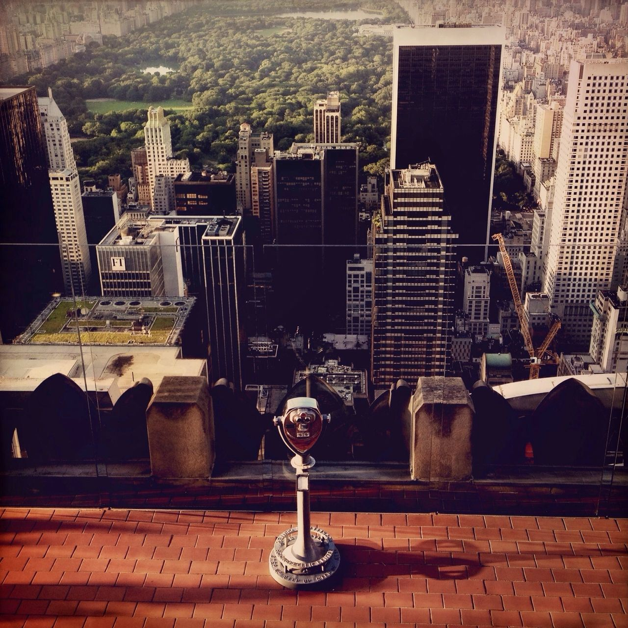 Coin operated binoculars against cityscape