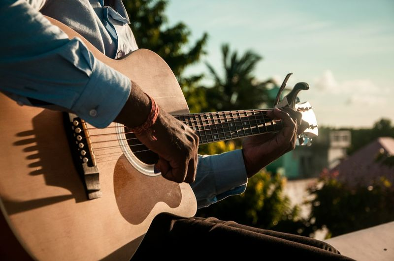 Midsection Of Man Playing Guitar On Sunny Day
