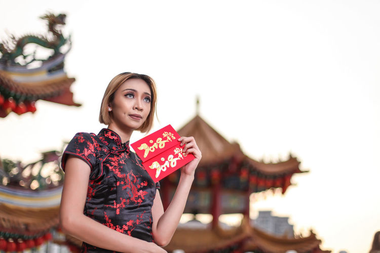 Low angle view of woman holding envelope against clear sky