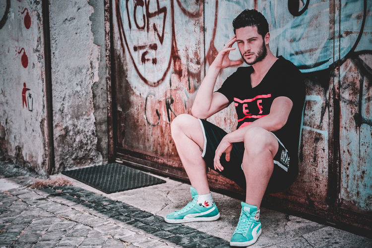 Full length of young man sitting on wall